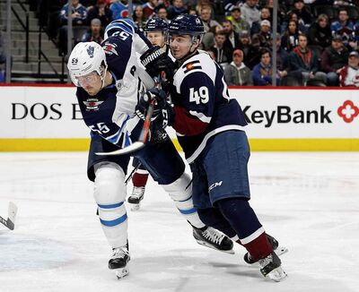 Colorado Avalanche defenceman Samuel Girard, right, checks Winnipeg Jets centre Mark Scheifele, left, as he pursues the puck in the second period Wednesday in Denver.