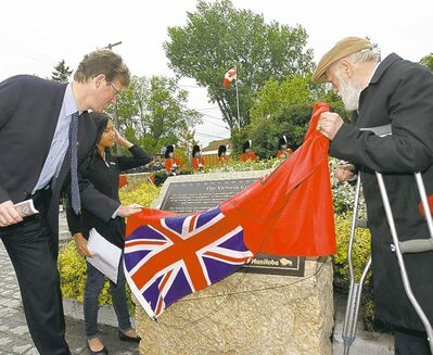 Justice Minister Andrew Swan, Clifton School student Clarisabel Catipon, 11, and Coun. Harvey Smith unviel one of four plaques during a dedication ceremony on Valour Road on Sunday.