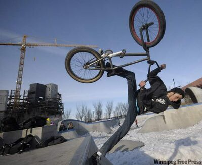 John West does a fast plant on his BMX bike at The Forks in the early spring.