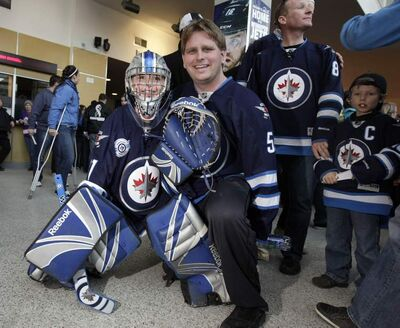 Cody Creasy, 8, with his dad, Shaun, from Brandon believe the Winnipeg Jets will make the playoffs, and Cody is ready to help out.