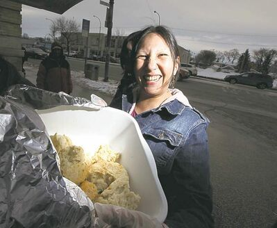 Althea Guiboche hands out bannock to passersby on Main Street at Dufferin Avenue Thursday afternoon.