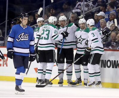 Dallas Stars' Mattias Janmark (13), Esa Lindell (23), Radek Faksa (12), Blake Comeau (15) and John Klingberg (3) celebrate after Faksa scored against the Winnipeg Jets. Jet Sami Niku (83) looks on during second period NHL hockey action in Winnipeg, Monday, March 25, 2019. Trevor Hagan / The Canadian Press