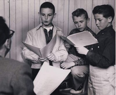 "June 23, 1958: ""Let me hear how you'd read that line."" John Hirsch, one of the directors of the Rainbow Stage, listens to three young aspirants for roles in The King And I. A notice of tryouts brought out a number of boys to fill the two important roles of the Young Prince and the son of Anna. Reading from left to right, these three aspirants are: Burton Cummings, 10, of 97 Lansdowne Ave; Fred Westman, 12, of 58 Crowson Bay; Jim McCarthy, 12, 263 Donalda Ave."