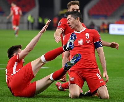 Robert Lewandowski of Poland, right, celebrates after scoring the third goal against Hungary during the FIFA World Cup 2022 qualifying soccer match between Hungary and Poland in the Puskas Ferenc Arena in Budapest, Hungary, Thursday, March 25, 2021. (Zsolt Szigetvary/MTI via AP)