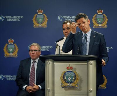 PHIL HOSSACK / WINNIPEG FREE PRESS FILES</p><p>Police Chief Danny Smyth (centre) and Mayor Brian Bowman, with police board chairman David Asper (seated), at a July media briefing to unveil the 2017 crime stats report.</p>