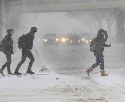Pedestrians scramble across Portage Avenue at Memorial Boulevard in downtown Winnipeg through blustery weather conditions today.