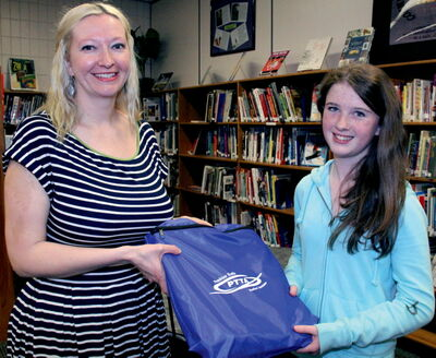 Ashleigh Deeley gives a new Kit to Acadia Junior High student Aoife Woods who recently moved to Winnipeg from Ireland.