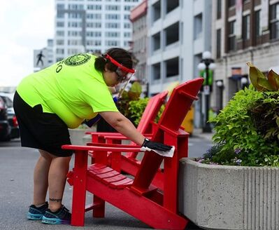 An employee disinfects a public chair in the Byward Market in downtown Ottawa on Monday, Aug. 17, 2020. THE CANADIAN PRESS/Sean Kilpatrick