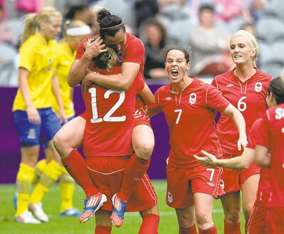 Frank Gunn / The Canadian PressCanada�s Melissa Tancredi jumps into the arms of Christine Sinclair to celebrate her second goal of the game.