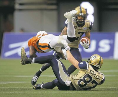 Darryl Dyck / THE CANADIAN PRESSThe B.C. Lions� Dante Marsh (left) collides with the Winnipeg Blue Bombers� Rory Kohlert (bottom) as Nick Moore carries the ball during the first half in Vancouver Friday.