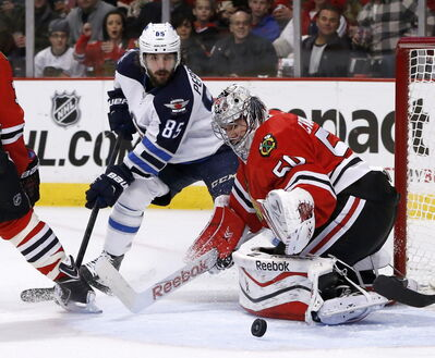 Chicago Blackhawks goalie Corey Crawford (50) makes a save as Winnipeg Jets centre Mathieu Perreault looks for a rebound on Tuesday in Chicago.