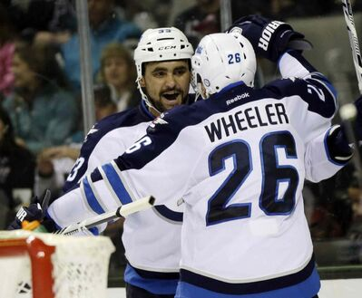 Winnipeg Jets' Dustin Byfuglien, left, celebrates his goal with teammate Blake Wheeler (26) during the second period.