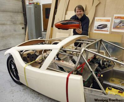 Jim Kor with the finished model and partially finished prototype two-seat, three-wheeled car called the Urbee.