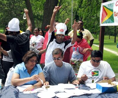 Roddy Premsukh (wearing chef's hat) and others dance behind the three judges, Farida Bacchus, Ramesh Mahadeo and Jagat James  during annual duck currie contest.