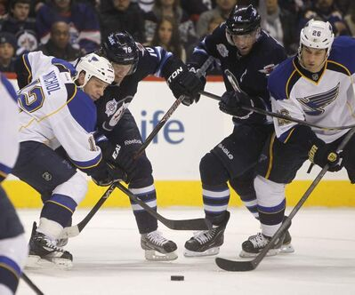 The Winnipeg Jets' Bryan Little (18) and Andrew Ladd (16) battle for the puck between the St. Louis Blues' Scott Nichol (12) and B.J. Crombeen (26) during second period NHL action at the MTS Centre, Saturday.