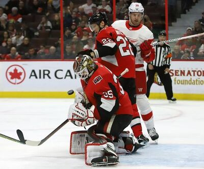 Ottawa Senators goaltender Marcus Hogberg (35) makes a save as teammate Nikita Zaitsev (22) and Detroit Red Wings right wing Anthony Mantha (39) look on during first period NHL hockey action in Ottawa, Saturday, Feb. 29, 2020. THE CANADIAN PRESS/Fred Chartrand