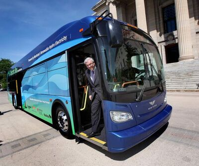 Premier Greg Selinger grins as he peers out of a new all-electric bus at the vehicle's unveiling Friday at the Legislature.