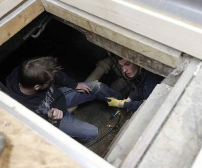 Working in a tight sub-floor crawlspace beneath Chocolatier Constance Popp are (from left) Chase Loewen and Jason Grundmann, a crew from Tractus Projects.
