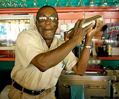 """Barbados mixologist Tommy Gibson teaches bar smarts to resort staff at the Almond. """"You have to shake the drink. You have to have flair with it. It's all mixology,"""" he says."""