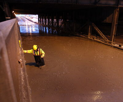 A city worker drains the flooded McPhillips Street rail underpass after a water-main break near Logan Avenue Monday morning.
