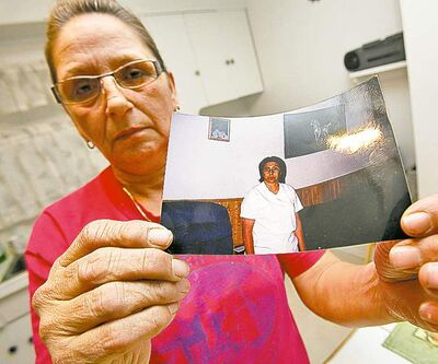 In her Selkirk home Tuesday, Sandra Hohne holds a photograph of her sister Gloria Sanderson who died in a fire Monday in Selkirk.