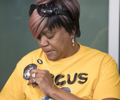 Renee Hill, mother of Calgary Stampeders defensive back Mylan Hicks, toiches a phot of her son while wearing a t-shirt commemorating her son at the sentencing of his killer in Calgary, Alta., Monday, March 11, 2019.THE CANADIAN PRESS/Jeff McIntosh