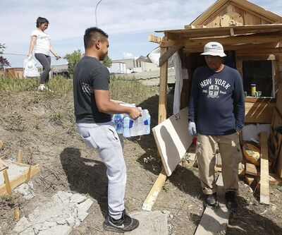 JOHN WOODS / WINNIPEG FREE PRESS FILES</p><p>A couple delivers water and food in July to Allan Par at the shack he built beside Omand's Creek. Par, who immigrated to Canada from the Philippines nine years ago, has returned home.</p>