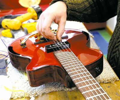 Allan Beardsell works on a guitar in his St. Matthews Avenue shop.