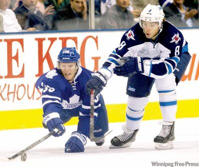 Maple Leafs defenceman Carl Gunnarsson battles for the puck with Winnipeg Jets centre Alexander Burmistrov in the first period.