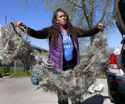 WAYNE GLOWACKI / WINNIPEG FREE PRESS</p><p>Cindy Kovach holds discarded fishing line and hooks she found on the eastern shore of the Red River north of the dam this spring. Littering is punishable by a fine of up to $190, but that doesn't deter everyone.</p></p>