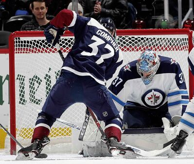 Winnipeg Jets goaltender Connor Hellebuyck, stops a shot off the stick of Colorado Avalanche left wing J.T. Compher in the second period.