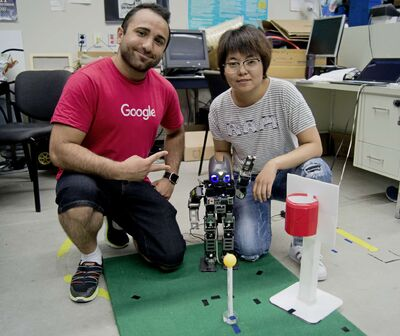 From left, Amir Hossein Memar and Qiuting Gong of the University of Manitoba's Autonomous Agents Laboratory pose with Jennifer the humanoid robot. It will be competing in basketball in the HuroCup from Aug. 23 to 27.