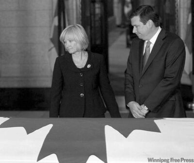 Stephen Harper's wife, Laureen, and Industry Minister Christian Paradis pay their respects.