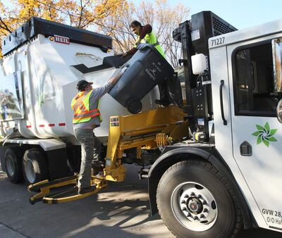 Garbage collectors retrieve an autobin they accidentally threw into their truck in the back lane of Elm Street in River Heights.