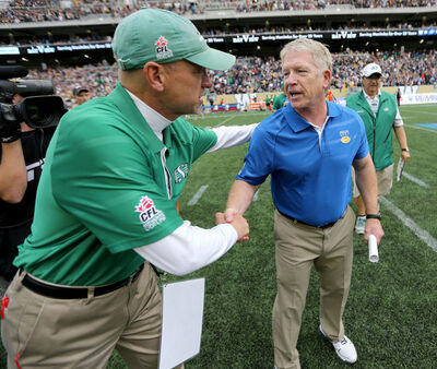 A member of the Saskatchewan Roughriders coaching staff congratulates head coach Tim Burke following the Bombers victory.