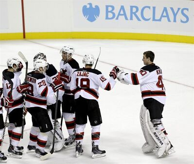 New Jersey Devils players celebrate after being the New York Islanders 3-0 during a preseason NHL hockey game, Saturday, Sept. 21, 2013, in New York. The match was the first ever hockey contest played at Barclays Center. (AP Photo/Julio Cortez)