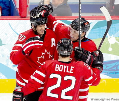 Canada's Dany Heatley, right, celebrates with teammates Dan Boyle and Chris Pronger after scoring the second goal against Norway at Canada Hockey Place Tuesday.