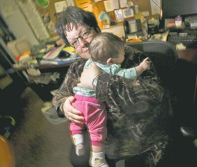 Barbara Judt, holding a resident's baby, worries about those who are abused by their spouses.