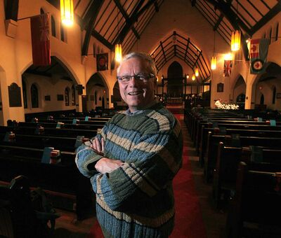 All Saints Anglican Church priest  Brent Neumann poses in the historic sanctuary Tuesday evening.