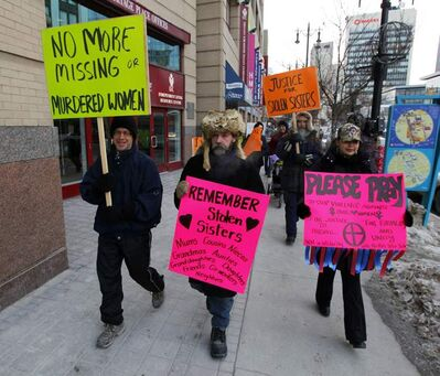 Marchers walk along the north sidewalk of Portage Avenue downtown as they head to a rally this morning at Portage Avenue and Memorial Boulevard.