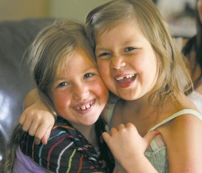 Six-year-old Sophia Penner (right) gets a loving hug from big sister Alexis, 7. Sophia has been doing remarkably well since her last treatment for leukemia.Ruth  Bonneville / Winnipeg Free Press