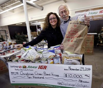 WAYNE GLOWACKI / WINNIPEG FREE PRESS</p><p>Natalina Porpiglia-Dafnis, specialist with Sobeys, presents Kai Madsen, executive director of the Christmas Cheer Board, with a $10,000 company donation cheque at the launch of the annual grocery donation bag campaign </p>