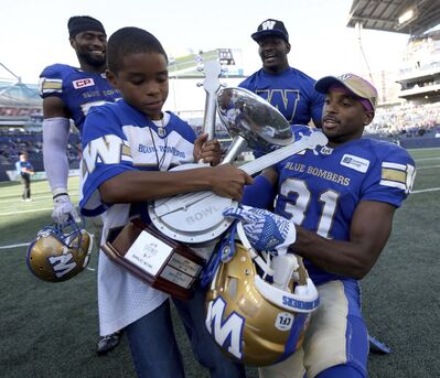 PHOTOS BY TREVOR HAGAN / THE CANADIAN PRESS</p><p>Malik Leggett (left), 9, celebrates with his dad, Winnipeg Blue Bombers&#39; Moe Leggett (31).</p>