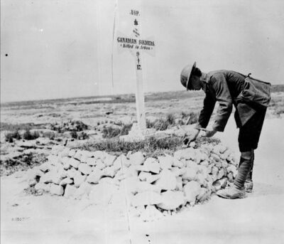 National Archives of Canada</p><p>A First World War soldier places stones on a Canadian's grave near Vimy, France, in June 1917. A century after it ended, many question why the war was fought.</p>