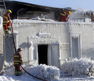Firefighters check for hot spots after an overnight fire destroyed the Knysh Funeral Chapel in Beausejour.