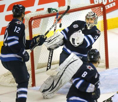 Winnipeg Jets netminder Ondrej Pavelec fights with the puck late in the first period at the MTS Centre Wednesday as he makes the save.