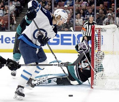 Anaheim Ducks goaltender John Gibson, back, defends the goal from Winnipeg Jets left wing Kyle Connor during the first period of an NHL hockey game in Anaheim, Calif., Wednesday, March 20, 2019. (AP Photo/Kyusung Gong)