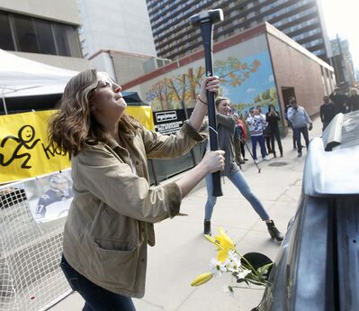 "PHIL HOSSACK / WINNIPEG FREE PRESS</p><p>Kerri Martens swings with enthusiasm at a derelect car at a downtown eatery Friday evening. Carbone Pizza organized the charitable ""Take a hammer and hit a car"" event. </p>"