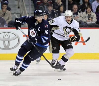 Winnipeg Jet captain Andrew Ladd deeks around Pittsburgh Penquin (19) Beau Bennett Thursday at the MTS Center in first period action.