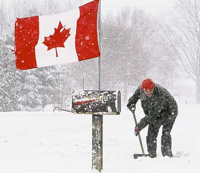 Dave Chidley / The Canadian PressRobert Marsh shovels a driveway in Newbury, Ont., Friday.